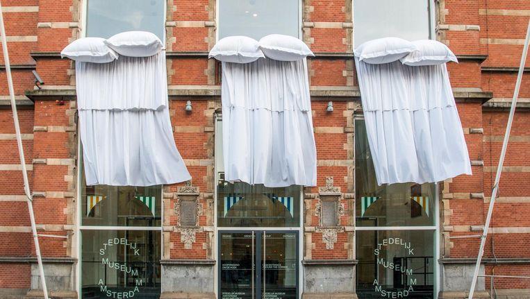 Voor alle ramen van het hoofdgebouw hangen wapperende witte lakens, op de kozijnen liggen dikke kussens. Beeld Jesper Boot