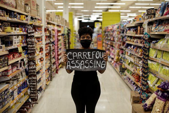 Een vrouw in een Carrefour-filiaal in Rio de Janeiro met een spandoek waarop de tekst 'Carrefour moordenaar' geschreven staat.