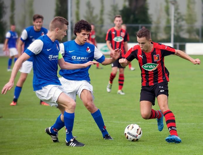Gaynio Aarts van Zundert in duel met Roosendaal-spelers Stanley Ammerlaan en Hans Frijters.