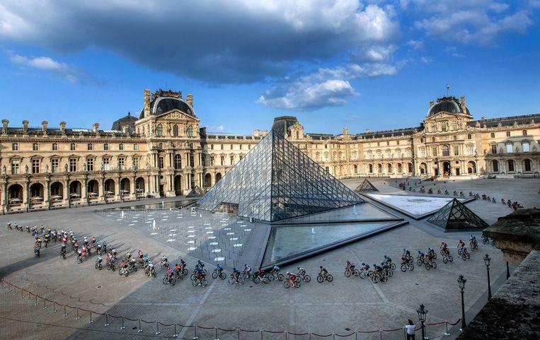 Het peloton fietst langs de piramide van het Louvre. Beeld EPA