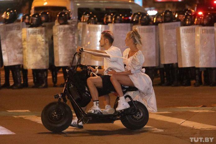 Een koppel rijdt voorbij een cordon politieagenten.