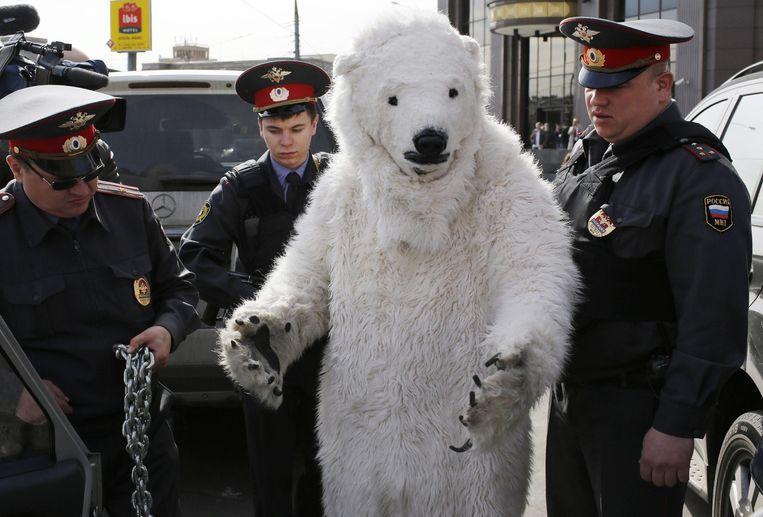 Russische agenten voeren een Greenpeace-activist in ijsbeerpak af. Beeld epa