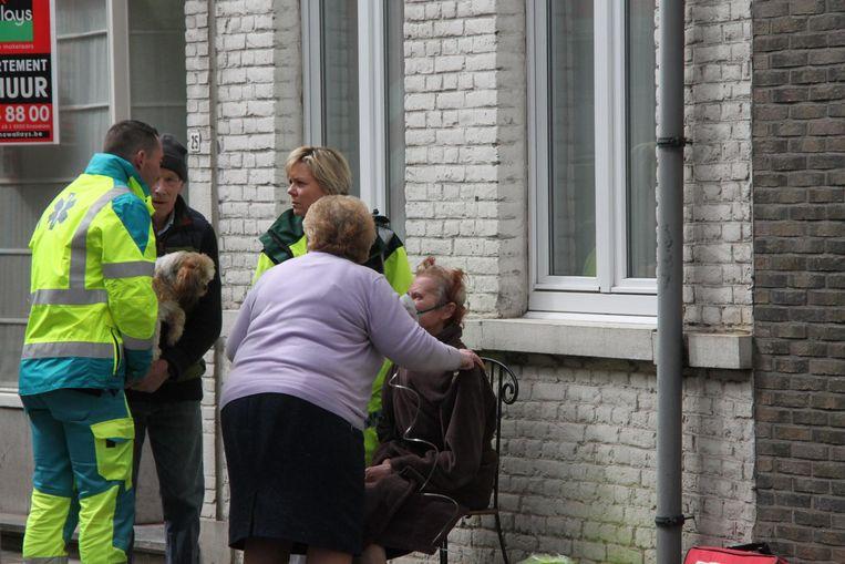 Etienne Vanryckeghem, echtgenote Liliane Vanderheeren en ambulanciers ontfermen zich over Rita Sintobin, die een zuurstofmasker draagt.