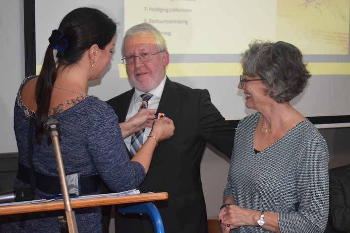 Burgemeester Hanne van Aart speldt de koninklijke onderscheiding op.