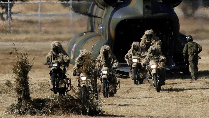 Leden van de Japanse luchtmacht komen tijdens een oefening op motoren uit een CH-47 JA transporthelikopter