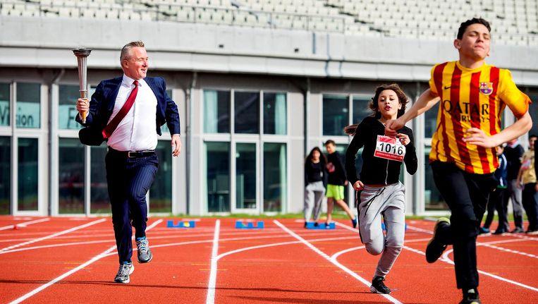 Wethouder Sport Eric van der Burg (L) strijdt met scholieren om een baanrecord op de atletiekbaan van het Olympisch Stadion. Beeld anp