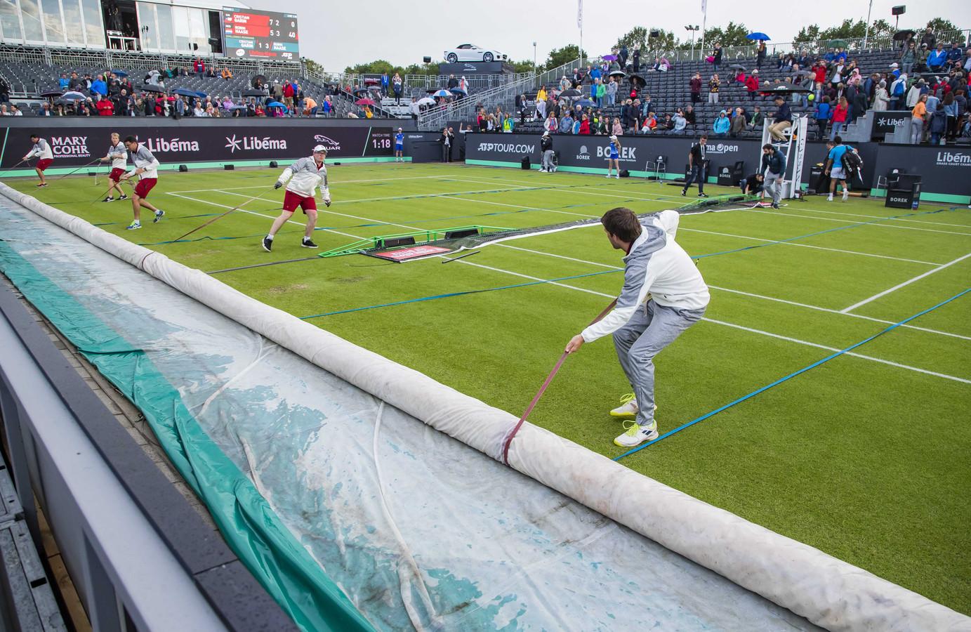 De baan wordt afgedekt tegen de regen tijdens de partij tussen Robin Haase en de Chileen Cristian Garin op het grastoernooi van Rosmalen.