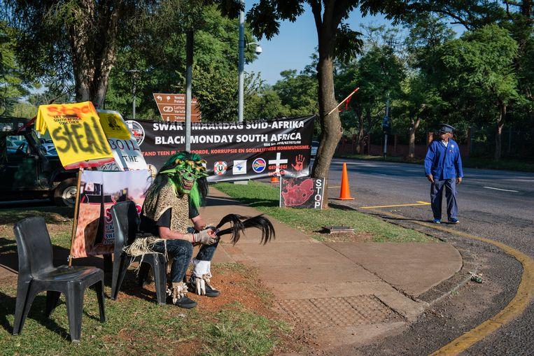 Een voorbijganger werpt een blik op het protest van de organisatie Swart Maandag. Op de stoel zit een man verkleed als Tokoloshe, een boze geest, die de lachwekkendheid van de ANC-regering moeten verbeelden.  Beeld Bram Lammers