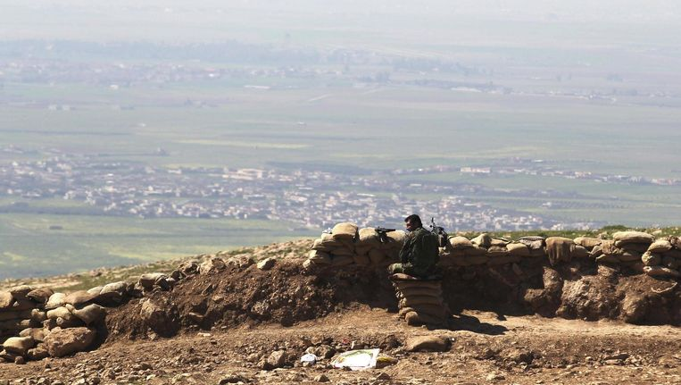 Een peshmergastrijder kijkt uit over een gebied twaalf kilometer ten oosten van de stad Mosul. Beeld Reuters