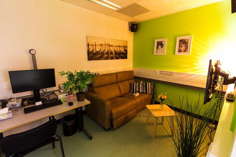 Het sekslab is ingericht als een woonkamer met zelfs wat planten en een bloemetje op tafel.