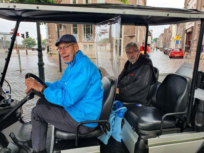 Voorzitter Jan Troost van Tourist Info Kampen rijdt Maarten van Rossem door de Kamper binnenstad in een golfkarretje.