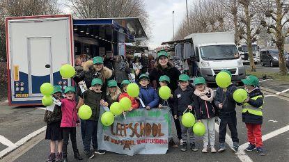 Kinderen De Dorpsparel delen ballonnen uit op markt