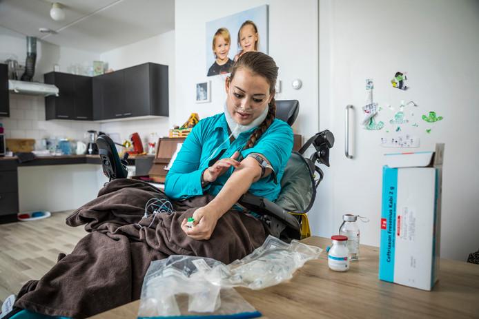 Saar Barten brengt een infuus aan. ,,Dat doe ik twee keer in de week zelf.'' Een beroep doen op de Thuiszorg is volgens haar geen optie. ,,Mijn hulpvraag is te groot.''  Foto henri van der beek