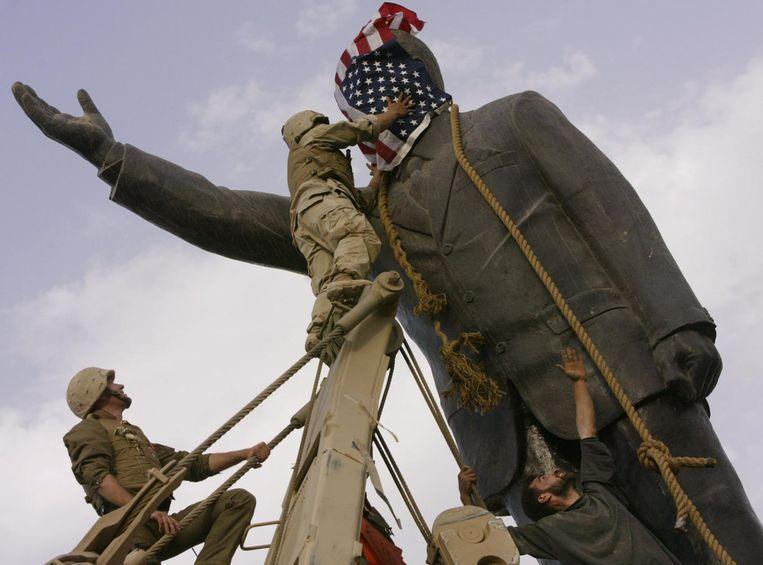 In 2003 trekken Irakezen in Bagdad, met hulp van Amerikaanse militairen, dictator Saddam Hoessein van zijn sokkel. Beeld ap