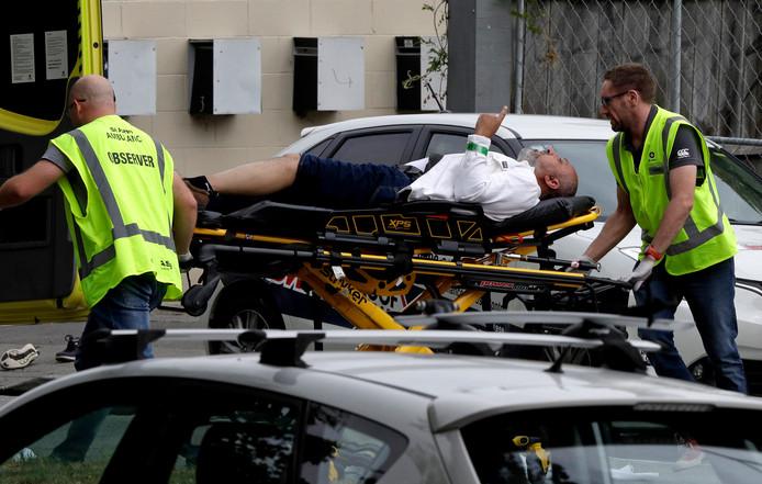 Ambulancemedewerkers vervoeren een van de slachtoffers naar het ziekenhuis. De man is gewond geraakt.