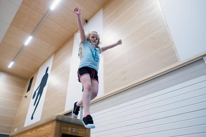 Elles (7) springt van de kast af tijdens de gym-extra-les in sportzaal Rozengaarde in Doetinchem.  Foto Jan van den Brink