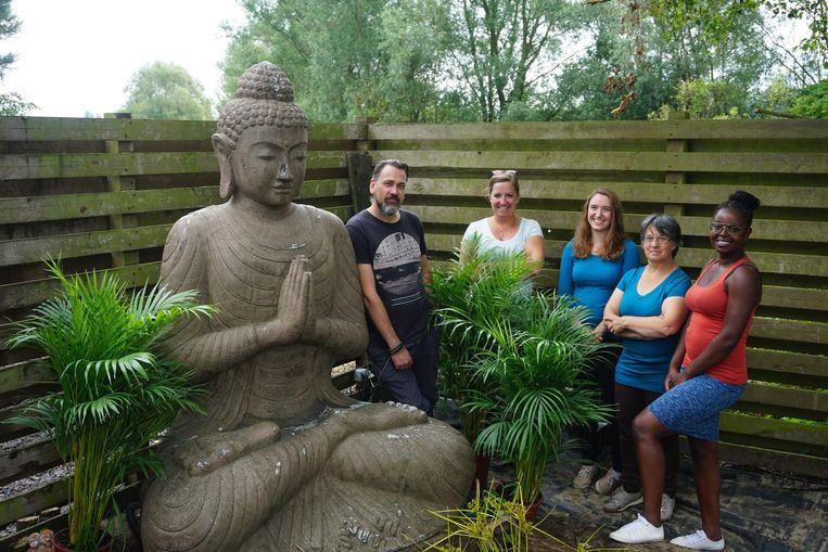 In de rustgevende tuin met boeddhabeeld. Kris Dumon, Bernadette Simoens, Emilie Peire, Marleen Lemmens en Anoda Mbuku Kasi hebben met vier andere coaches de vzw Groei opgericht.