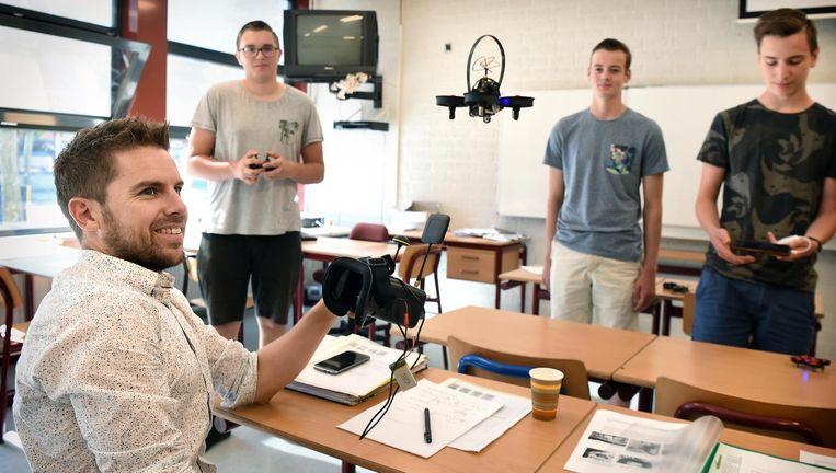 Rik Adriaans als hybride docent aan het werk aan het Eckartcollege in Eindhoven. Leerlingen presenteren een project met een drone. Beeld Marcel van den Bergh