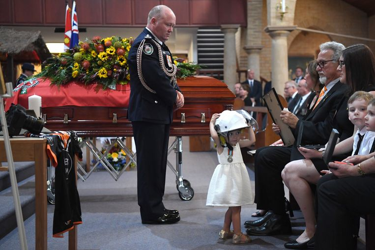 Charlotte (negentien maanden oud) draagt de helm van haar held tijdens de plechtigheid.