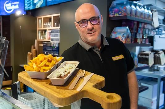 Antoine van Vugt van  eetwinkel Kwebbles in Geertruidenberg met een frikandel speciaal en frietjes in de milieuvriendelijke bakjes.