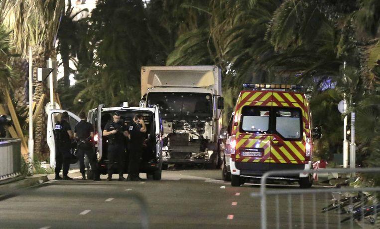 Politieagenten houden de wacht naast de vrachtwagen die in de menigte reed. Het raam lijkt bezaaid te zijn met kogelgaten.