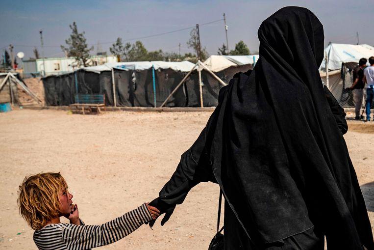 Een Franse vrouw houdt de hand van haar kind vast in het kamp Al Hol in Syrië.  Beeld AFP