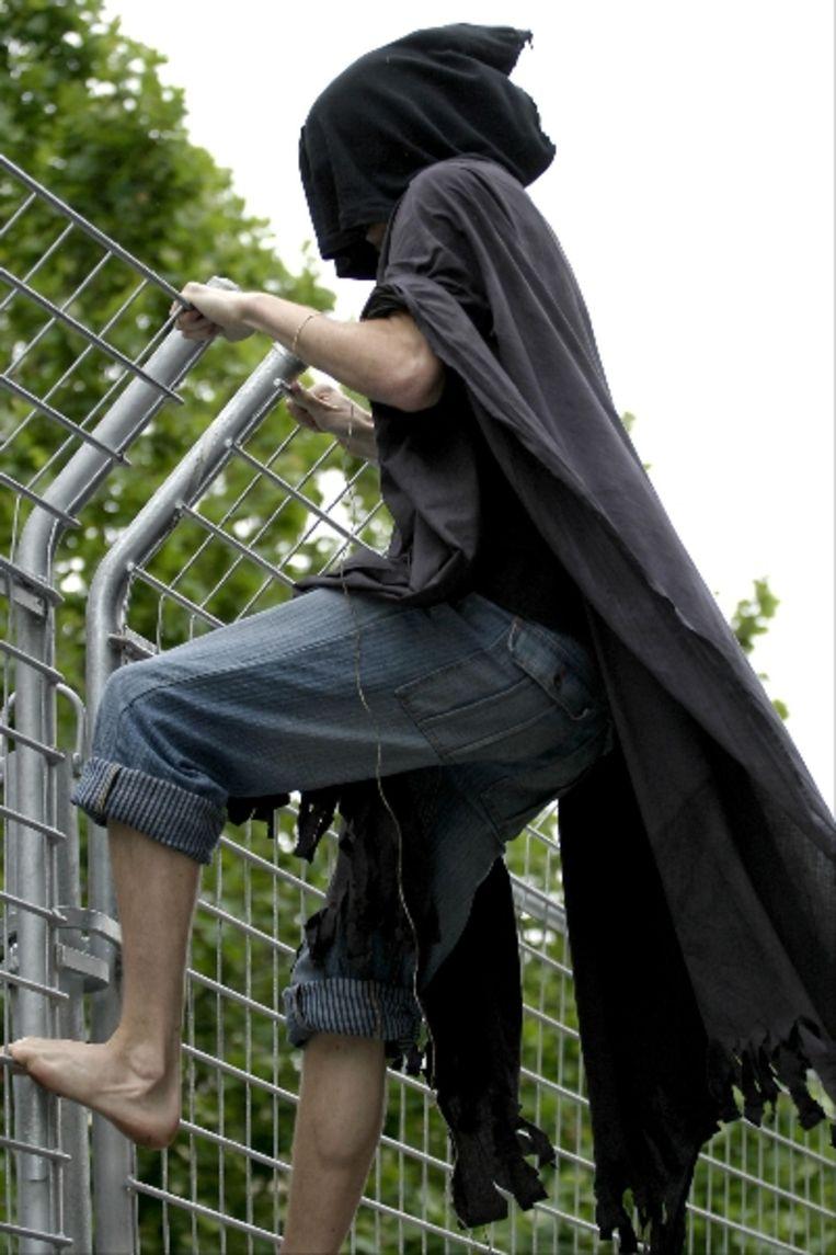 Een tegenstander van de oorlog in Irak heeft zichzelf verkleed als Aboe Ghraib gevangene en is op een hek geklommen van een gemeentehuis in Adelaide, Australië. In het gemeentehuis bevindt zich onder andere Donald Rumsfield. (AFP) Beeld AFP