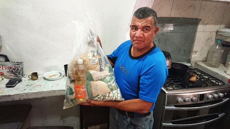 Buurtleider Yoel Capriles met een voedselpakket van de regering.  Beeld Edwin Koopman