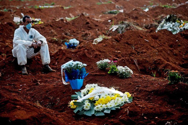 Een grafdelver van de begraafplaats Vila Formoso in het Braziliaanse São Paulo, afgelopen maandag. In twaalf uur tijd vonden daar 62uitvaarten plaats.  Beeld Fernando Bizerra / EPA