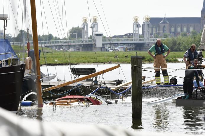 De brandweer probeert het water uit de boot te pompen.