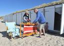 John en Rian Vernooij uit Breda haalden zaterdag hun strandkotje leeg. Kleindochter Kaat kijkt beteuterd toe.