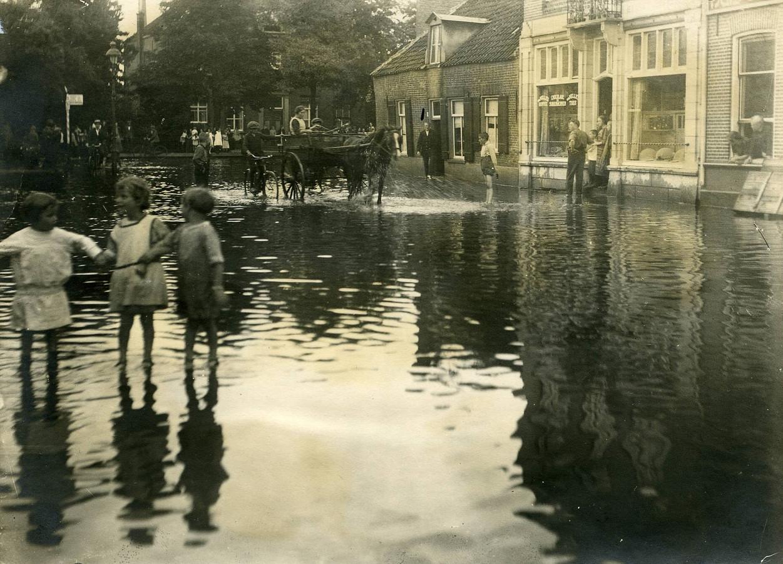Het Walplein in Oss staat blank na een wolkbreuk in 1925. Veel Ossenaren vonden het gebeuren 'attractioneel'. Op de achtergrond achter de bomen staat de hervormde pastorie, nu nog V&D.
