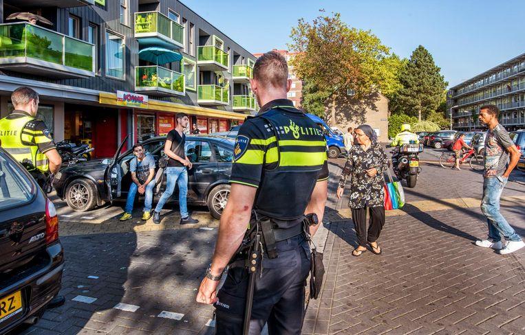 Politie bij de supermarkt in de wijk Poelenburg in Zaandam. Beeld Raymond Rutting / de Volkskrant