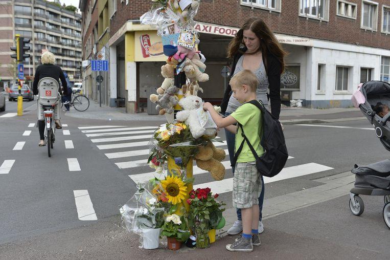Dylan (7) hangt samen met zijn mama Kelly Van de Merlen een knuffelbeer op de plaats waar de 6-jarige Ziggy maandag is verongelukt.