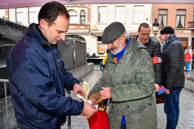 De bedeling van de polsbandjes begint. Pierre Annerel zat donderdag als eerste aan de Grote Markt en krijgt het eerste bandje.