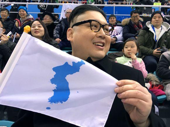Een lookalike van de Noord-Koreaanse leider Kim Jong-un met de verenigingsvlag op de Winterspelen.