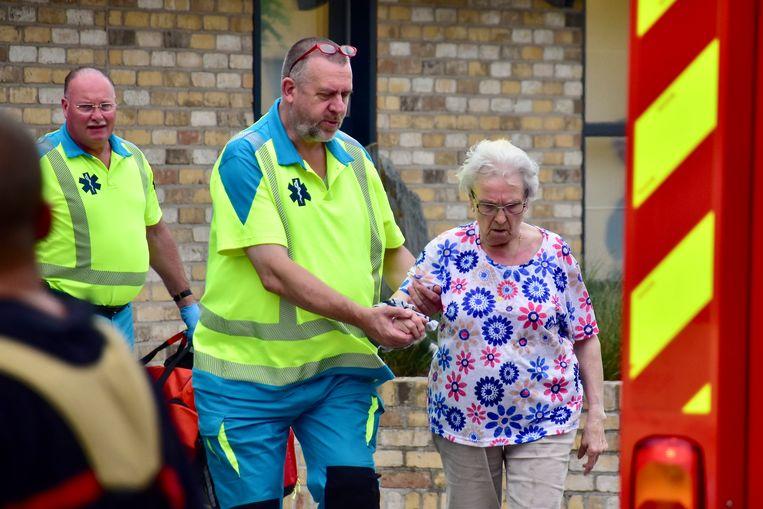 Een ambulancier van de brandweerpost Wervik begeleidt Dina Vantomme, op weg naar de ambulance.