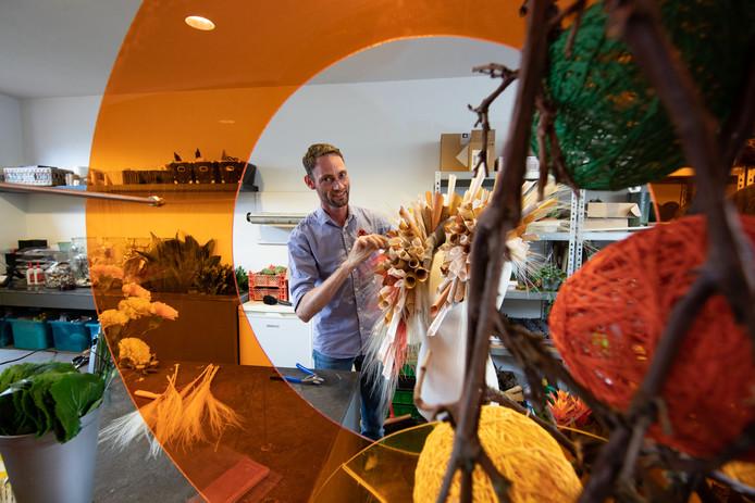 Johannes de Boer werkt in zijn bloemenzaak aan een van de opdrachten. ,,De cirkels daar hou ik van, het geeft een beetje het leven weer.''