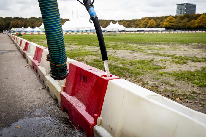 Een afzetting op het Malieveld wordt dinsdag door een boer gevuld met water. Den Haag maakt zich op voor een nieuw boerenprotest.