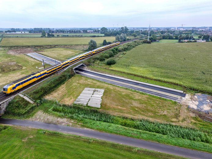 Een brede tunnel met twee banen asfalt onder het spoor door. Midden tussen de weilanden ten westen van De Hoven ligt een klein deel van de rondweg De Hoven al twee jaar te wachten op auto's en vrachtwagens.