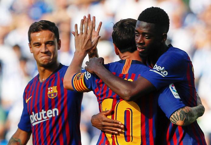 Ousmane Dembélé (rechts) viert zijn goal met Lionel Messi en Philippe Coutinho (links).