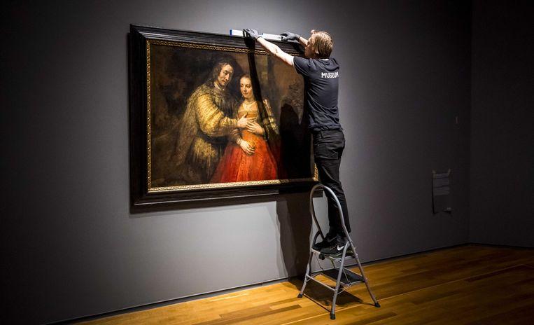 Het schilderij Het Joodse Bruidje van Rembrandt van Rijn wordt opgehangen in het Rijksmuseum voor de opening van de tentoonstelling Alle Rembrandts.  Beeld ANP