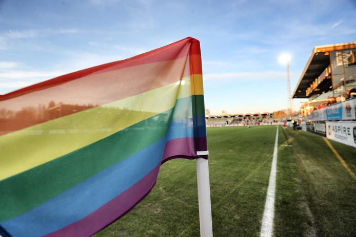 Een regenboogvlag langs een voetbalveld