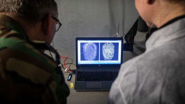Forensische onderzoekers van de landmacht demonstreren hoe zij vingerafdrukken vergelijken. Beeld Jarno Kraayvanger/Defensie
