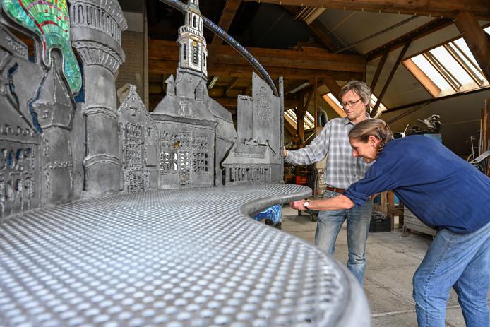 Bert Jurling en Linda Verkaaik leggen de laatste hand aan het Gedichtenbankje dat donderdag in Nijkerk wordt onthuld.