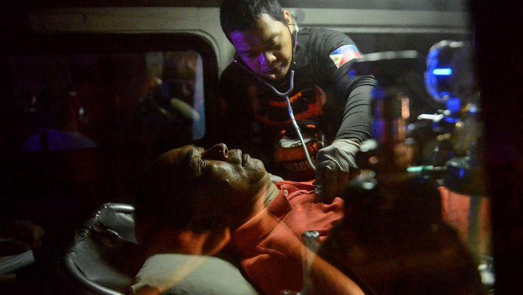 Een slachtoffer wordt behandeld in een ambulance buiten het casino in Manilla. Beeld null