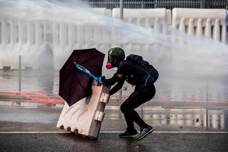 Een demonstrant in Hongkong, bewapend met tennisracket, zoekt achter een paraplu dekking voor het waterkanon van de politie. Beeld null