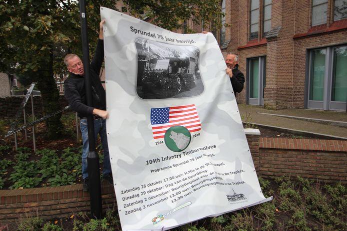 Vrijwilliger Frans Aarts (links) ontrolt met Jac van Trijp de vlag die tijdens de komende bevrijdingsactiviteiten naast de kerk in Sprundel wappert.