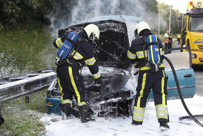 Brandweerlieden hebben de in brand gevlogen auto geblust.