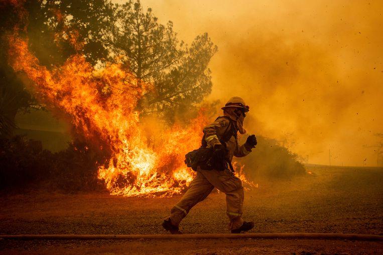 Een brandweerman in Californië haast zich om een huis te beschermen tegen de natuurbrand. Beeld AP